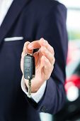 picture of showrooms  - Seller or car salesman in car dealership with key presenting his new and used cars in the showroom - JPG