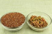 picture of quinoa  - Uncooked red quinoa seeds in a round clear glass dish next to a tasty and healthy appetizer bowl of cooked quinoa mixed with jalapeno slices - JPG