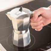 Italian Coffee Pot In Hand On A Black Electric Cooker.