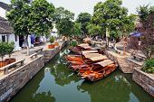 foto of tong  - Photo of a canal in ancient Tongli watertown near Suzhou China with traditional boats and old houses on both sides filtered and stylized to resemble an oil painting - JPG