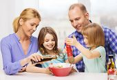 food, family, children, happiness and people concept - happy family with two kids making dinner at home