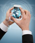 business, internet and technology concept - businessman touching screen of smartphone with globe hologram on it
