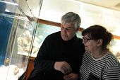 Senior Couple Watching Fishes In Aquarium