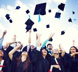 stock photo of graduation gown  - Graduation Caps Thrown in the Air - JPG
