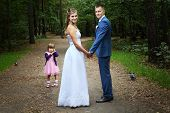 stock photo of fiance  - On the day of their wedding the newlyweds walk on summer forest afternoon with a girl three years - JPG