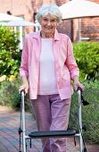 Elderly Lady Using A Walker In The Garden