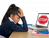 stock photo of stop bully  - hispanic sweet little girl crying and suffering internet bullying and abuse at school sitting at desk with computer and stop sign - JPG