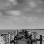 stock photo of sea-scape  - A shot of groynes jutting out into the sea. Taken with a long exposure to make the clouds and water misty. ** Note: Visible grain at 100%, best at smaller sizes - JPG