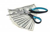 Scissors lying down on batch of dollars isolated in white