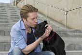 Happy Young Man Kissing His Dog