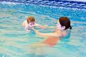 Baby Girl Swimming With Her Mother In A Pool