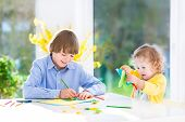 Two Adorable Kids drawing, painting and cutting colorful paper butterflies