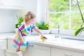 Cute Curly Toddler Girl washing dishes, cleaning with a sponge and playing with foam in the sink