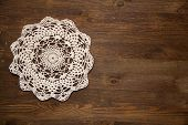 Crochet doily over dark wood