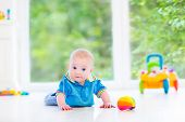 Adorable Baby Boy Playing With A Colorful Ball And Toy Car In A Sunny Nursery With White Furniture