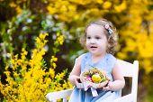 Cute Curly Toddler Girl Enjoying Easter Egg Hunt In The Garden