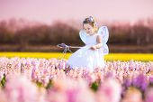 image of fairy  - Portrait of an adorable toddler girl in a magic fairy costume and flower crown in her curly hair playing with a wand in a beautiful field of purple hyacinths in Keukenhof Holland on windy spring day - JPG