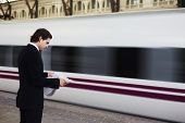 Handsome businessman stand on train railway station with motion blur of train on background, busines