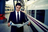 Adult serious businessman reading newspaper standing in platform of big railway station, successful