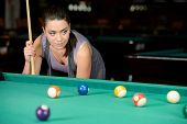 Young woman playing billiards