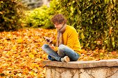 Curly Man In Blue Jacket With Computer Tablet In Autumn