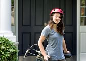 Teenage Girl Wearing Helmet While Resting On Bicycle Outdoors Near Home