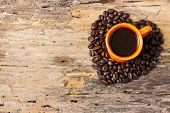 Cup Of Black Coffee And Coffee Beans Arranged In Heart Shape On Wooden Background.