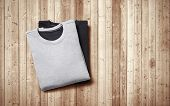 Two Blank Jumpers Lying On Wood Background