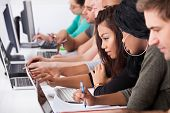 Female College Students Using Laptop At Desk