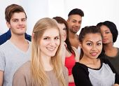 Portrait Of College Students Standing In Classroom