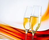A Pair Of Champagne Flutes With Golden Bubbles On Blur Light Background