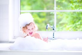 picture of big-girls  - Funny little baby girl with wet curly hair taking a bath in a kitchen sink with lots of foam playing with water drops and splashes next to a big window with garden view - JPG
