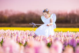 picture of princess crown  - Portrait of an adorable toddler girl in a magic fairy costume and flower crown in her curly hair playing with a wand in a beautiful field of purple hyacinths in Keukenhof Holland on windy spring day - JPG