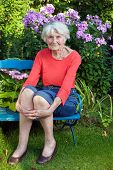 Smiling Old Woman Sitting On The Garden Bench
