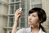 Angry business woman of Asian holding cellphone and looking at it in outside of office in Taipei, Taiwan, Asia.