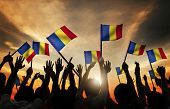 Group of People Waving Romanian Flags in Back Lit