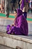 Indian Women In Purple Sari Sitting Near The Lake At Golden Temple. Amritsar. India