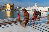 Indian Women And Children Clean Floor Near Golden Temple Before The Evening Prayer. Amritsar