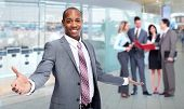 Happy young African-American man in office background