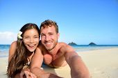 Couple relaxing on beach taking selfie picture with camera smartphone. Young multiracial couple on getaway vacation in Hawaii lying down looking at camera. Candid closeup angle looking candid real.