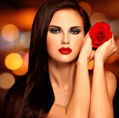 Pretty adult girl holding red rose in hands. Beautiful model posing at studio with bright red lipstick on the lips