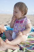 Baby Eating Banana At Beach