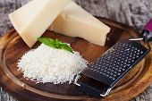 stock photo of metal grate  - grated parmesan cheese and metal grater on wooden board - JPG