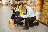 stock photo of industrial safety  - Manager training worker for health and safety measure in a large warehouse - JPG
