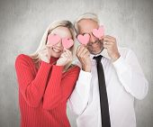 Silly couple holding hearts over their eyes against weathered surface