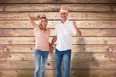 Happy couple walking holding hands against wooden planks background