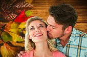 Handsome man kissing girlfriend on cheek against wooden table with autumn leaves