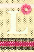 Wooden letter L on polka dots background