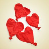 some deflated heart-shaped balloons on a beige background, with a retro effect