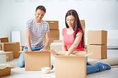 Young couple unpacking boxes in their new flat